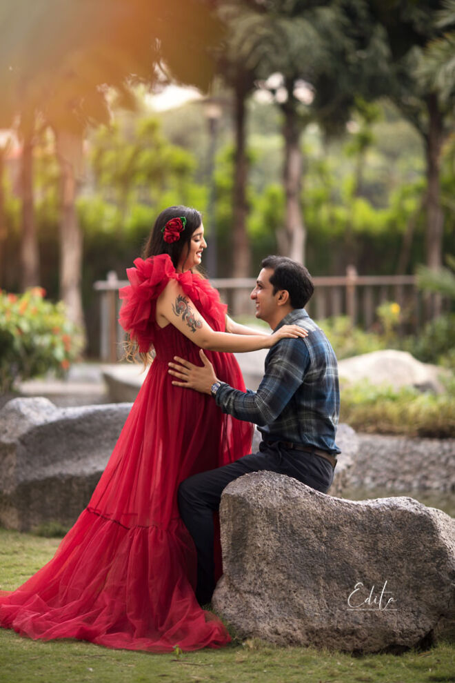 Pregnancy couple photoshoot in garden in red long tulle gown