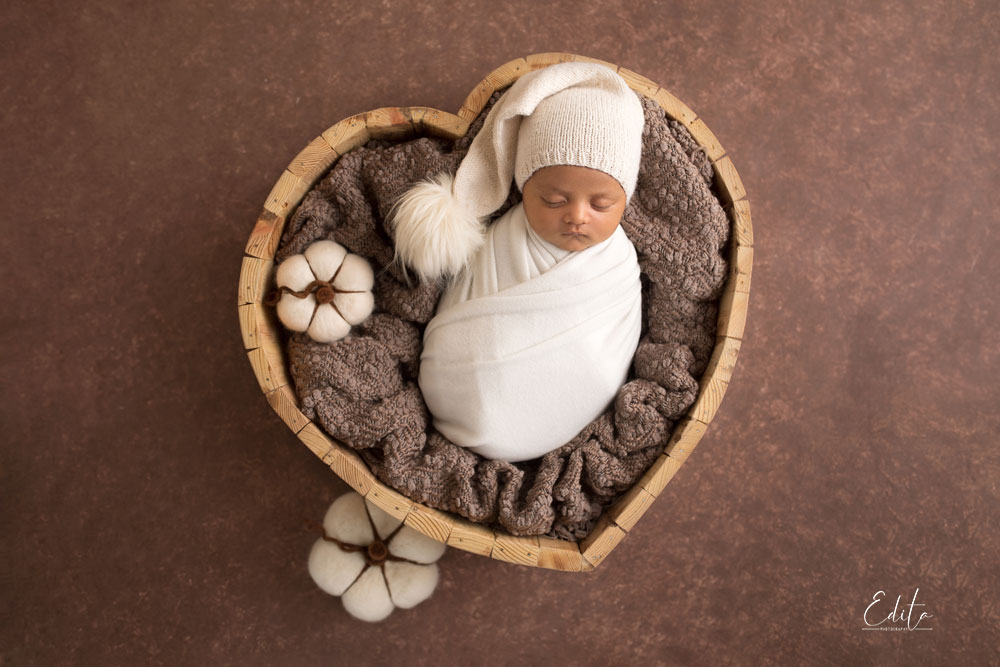 Inspiring newborn photos in heart shaped bowl with brown background and white wrap