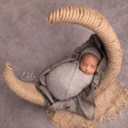 Newborn boy posed on rustic moon prop