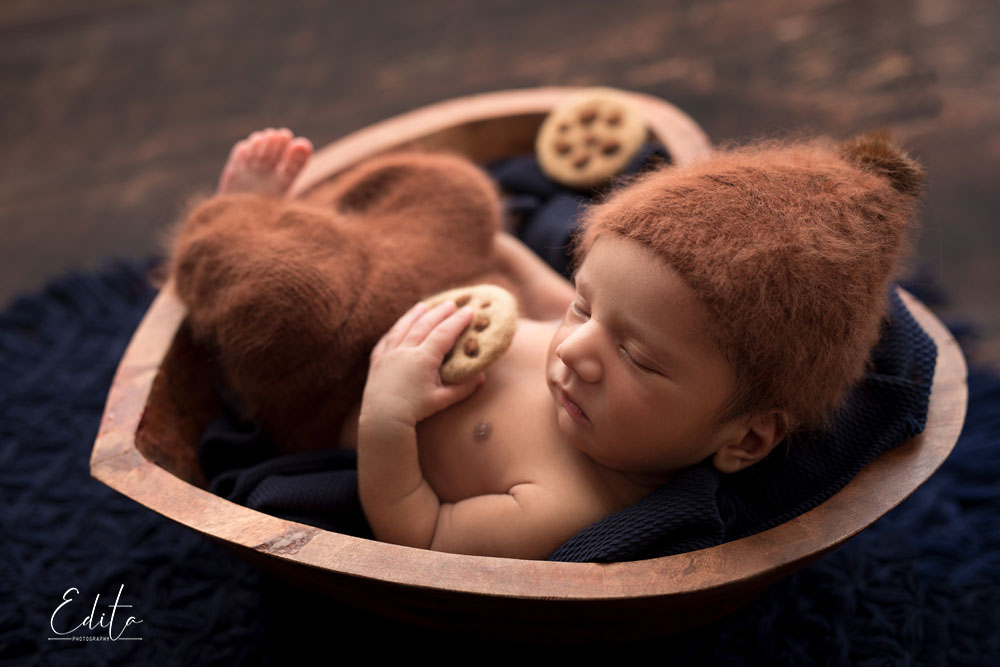 baby boys in heart shape bowl holding biscuit backlit photo