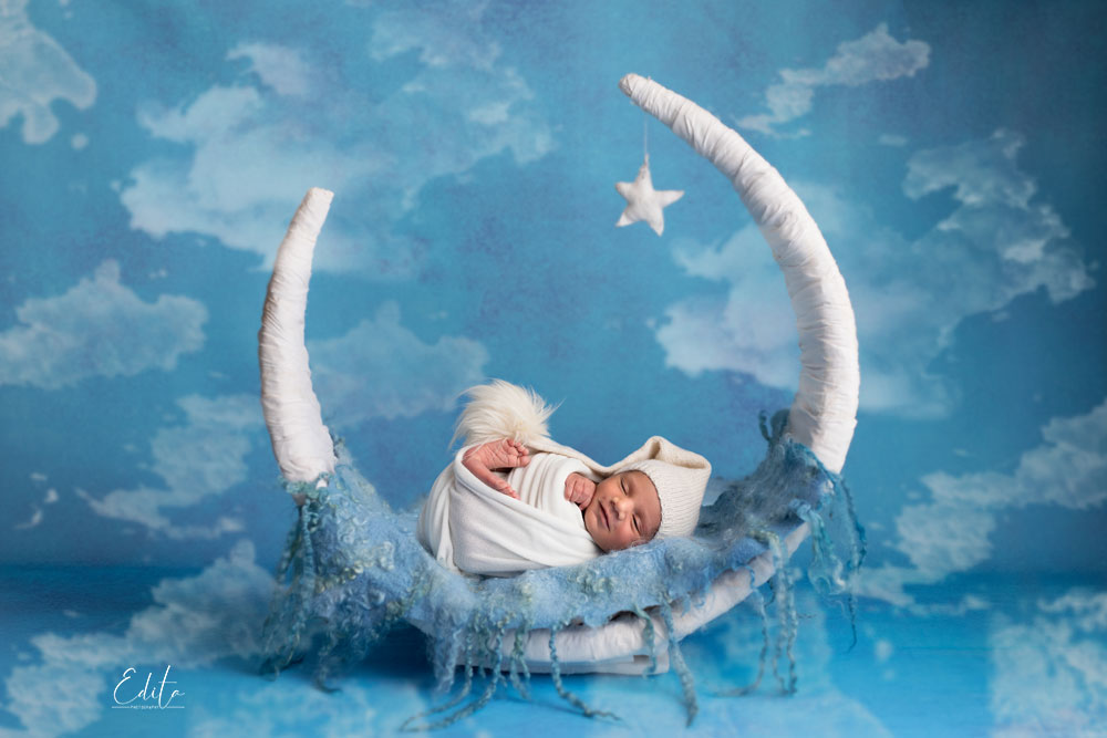 Newborn baby boys in white wrap on the moon prop and blue background with clouds
