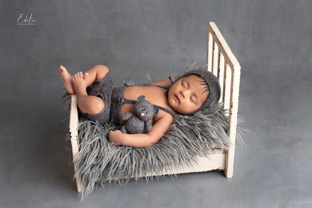 Baby boy in grey on white tiny bed with mini toy
