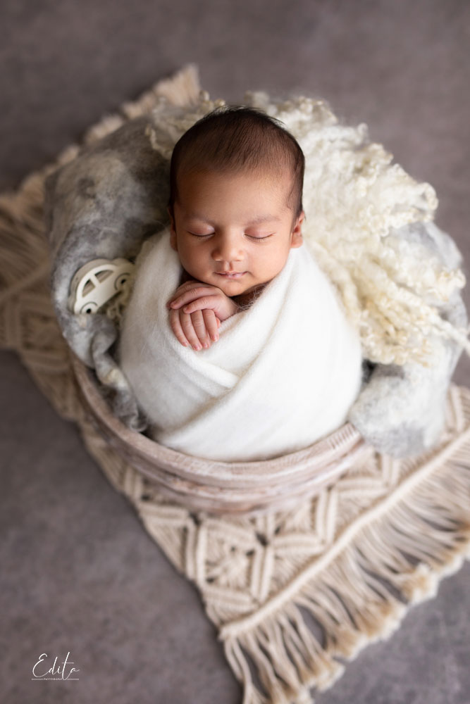 baby boy in white wrap posed in wooden bowl placed on macrame