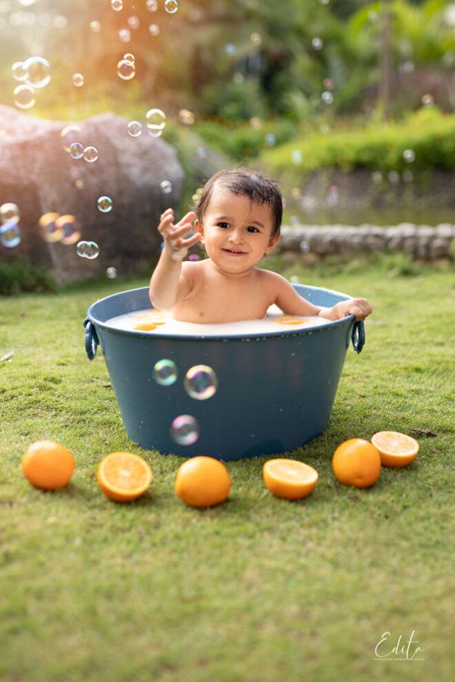 Toddler boy milk bath with oranges in the garden sunset golden hour backlit photo