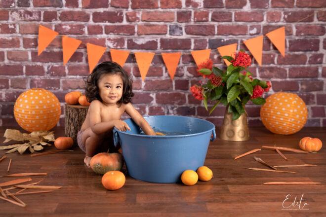 Toddler boy in autumn pumpkin setup